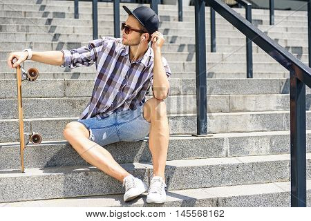 Cool young man is sitting on stairs and holding skate. He is listening to music from earphones with pleasure and relaxing