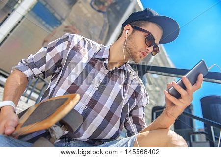 Thoughtful male skater is enjoying music from smartphone. He is wearing headphones and looking at gadget with concentration. Man is sitting on staircase and carrying skate