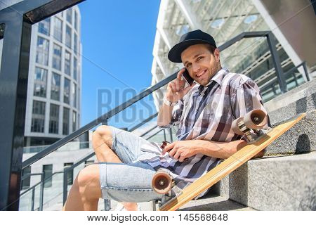 Joyful young man is using phone for communication. He is looking at camera and smiling. Guy is sitting on steps near his skate