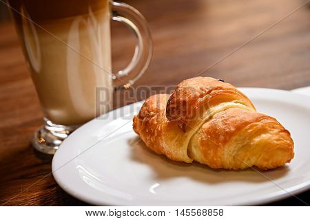 breakfast with cup coffee and croissant in bakery