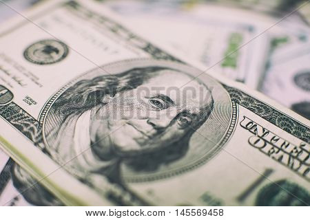 A stack of money. Heap of one hundred dollar bills on money background. Fake money. Shallow depth of field. Selective focus.