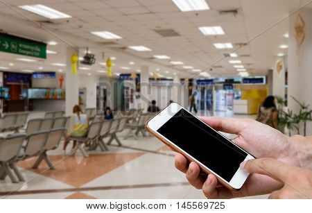 Human holding blank screen of smart phone and waiting arrivals time background blur.