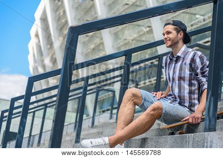 Happy male skateboarder is resting on stairs and smiling. He is sitting and carrying skate. Man is looking forward with joy