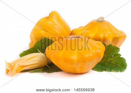 three yellow pattypan squash with leaf and flower isolated on white background.