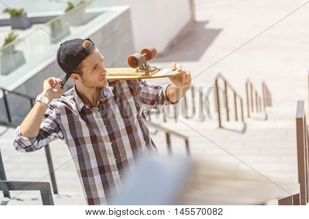 Pensive male skateboarder is standing on stairs with skate. Man is touching his cap and looking forward with confidence