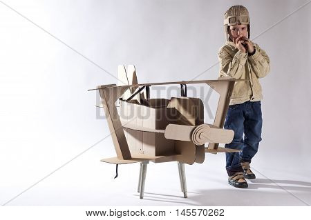 Young aviator in a homemade cardboard aircraft on white background.