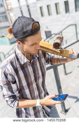 Serious young man is sending message on smartphone. He is standing and holding skate