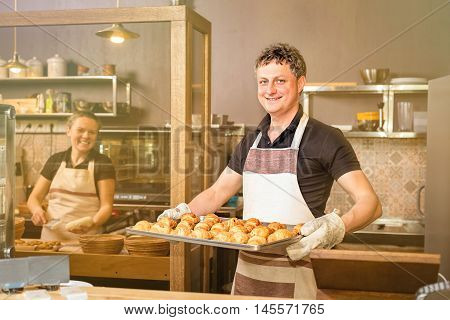 baker concept. Happy baker showing tray of fresh croissant in the kitchen of the bakery
