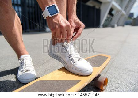 Close up of male legs standing on skateboard. Man is tying laces on his sneakers. He has smart watch on his hand