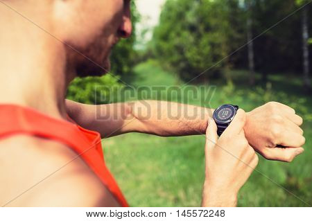 Runner on mountain trail looking at sportwatch checking direction on electronic compass performance or heart rate pulse with smart watch. Sport training and fitness motivation inspiration outdoors.