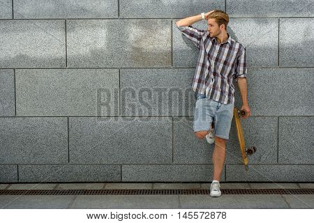 Handsome young man is standing and posing near wall. He is holding skate. Skater is touching his hair and looking aside flirtingly. Copy space in left side