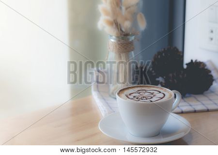 hot coffee with foam milk art. Hot coffee in afternoon break. coffee mocha on the wood desk.(selective focus vintage effect)