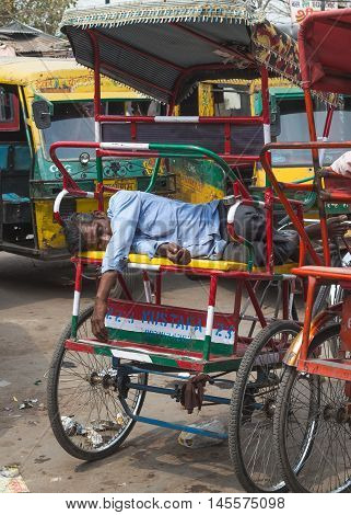DELHI INDIA - 19TH MARCH 2016: A man asleep on a tuk tuk during the day in Delhi India