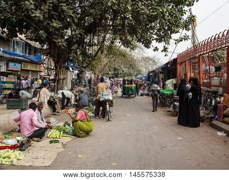 DELHI INDIA - 19TH MARCH 2016: Streets of Delhi with people selling fruit and vegetables at the side of the road.