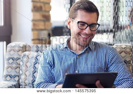 With positivity in mind. Cheerful bearded delighted man smiling and using tablet while resting on the couch in the cafe