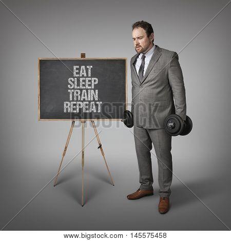 Eat sleep train text on blackboard with businesssman holding weights