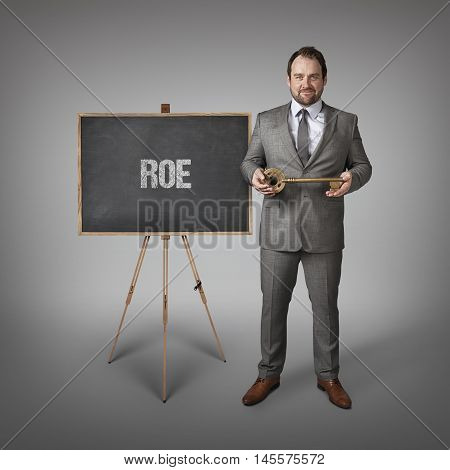 ROE text on  blackboard with businessman and key