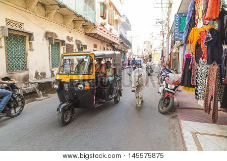 UDAIPUR INDIA - 20TH MARCH 2016: A view along streets of Udaipur during the day. People shops Tuk Tuks and a cow can be seen.