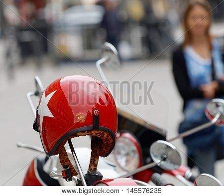 STOCKHOLM SWEDEN - SEPTEMBER 03 2016: Red shining retro helmet on the handlebar of a vespa scooter a woman in the background before the start of the Mods vs Rockers event at the Saint Eriks bridge Stockholm Sweden September 03 2016