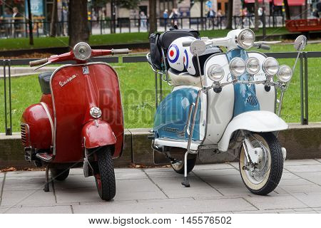STOCKHOLM SWEDEN - SEPTEMBER 03 2016: Two beautiful red and blue/white retro vespa scooters parked before the start of the Mods vs Rockers event at the Saint Eriks bridge Stockholm Sweden September 03 2016