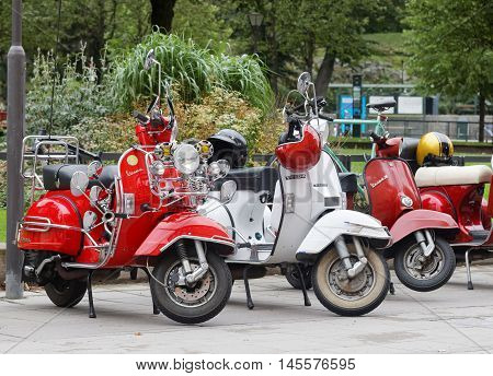 STOCKHOLM SWEDEN - SEPTEMBER 03 2016: Three beautiful red and white retro vespa scooters parked before the start of the Mods vs Rockers event at the Saint Eriks bridge Stockholm Sweden September 03 2016
