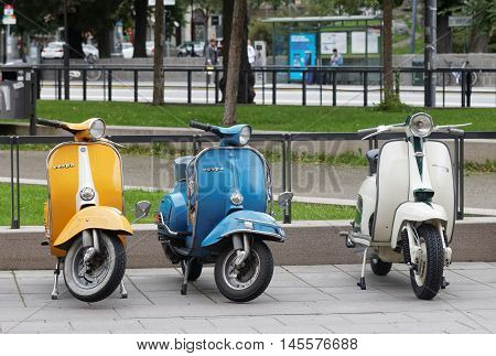 STOCKHOLM SWEDEN - SEPTEMBER 03 2016: Three beautiful yellow blue and white retro vespa scooters parked before the start of the Mods vs Rockers event at the Saint Eriks bridge Stockholm Sweden September 03 2016