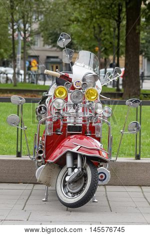 STOCKHOLM SWEDEN - SEPTEMBER 03 2016: Red retro vespa scooter with many rear-view mirrors and spotlights before the start of the Mods vs Rockers event at the Saint Eriks bridge Stockholm Sweden September 03 2016