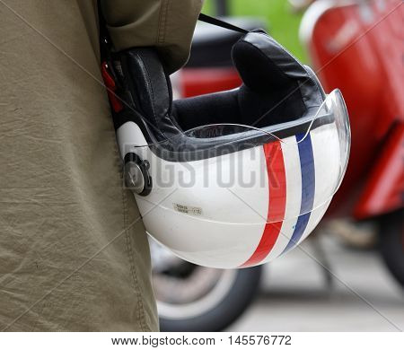 STOCKHOLM SWEDEN - SEPTEMBER 03 2016: Closeup of a retro helmet carried by a man before the start of the Mods vs Rockers event at the Saint Eriks bridge Stockholm Sweden September 03 2016