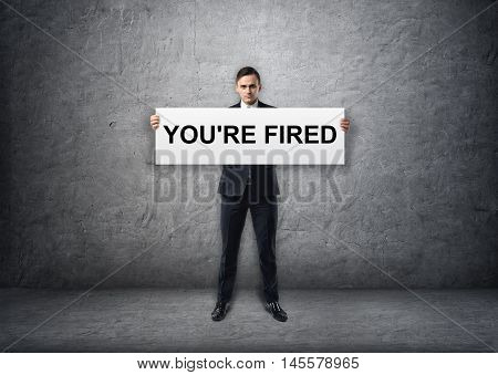 Businessman holding banner with 'you're fired' text on it in his hands. Jobless. Unemployed. Discharged employee. Losing a job.