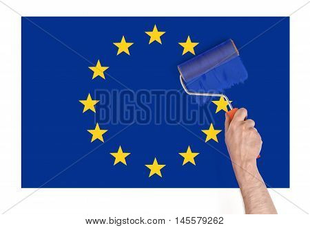 Close up view of a man's hand painting over a star on Europe Union flag. Brexit. British withdrawal. Euroscepticism.