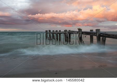 A weathered and broken pier located near Burlington Ontario taken at sunset and twilight.