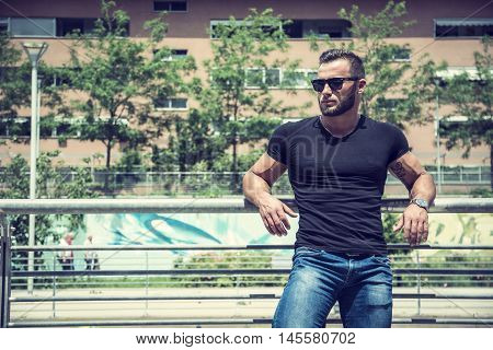 Handsome muscular blond man standing in city setting or former industrial environment