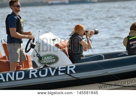04.09.2016.Russia.Saint-Petersburg.The girl-photographer takes a regatta boaters on the river.