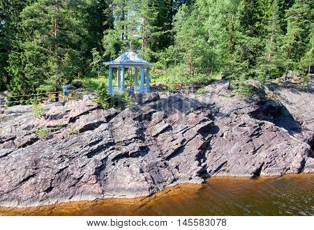 IMATRA, FINLAND - JULY 2, 2016: Man takes pictures near pavilion in front of the canyon of Imatrankoski (The Imatra Rapid) on The Vuoksi River.