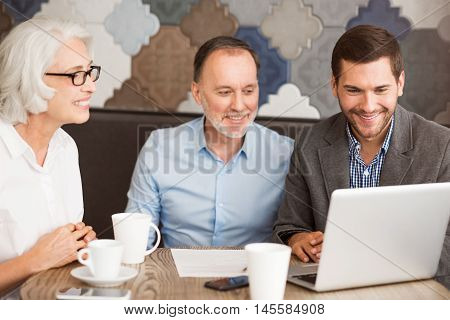 I know my work. Positive professional sales manager sitting at the table and using laptop while working with his clients