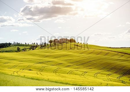 Beautiful tuscan landscape view on the green field with farmhouse near Pienza town in Italy