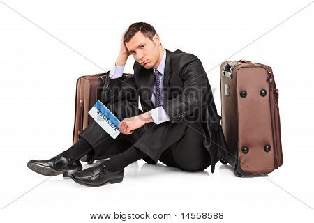Sad Business Traveler Seated Next To A Suitcase With A Ticket In His Hand