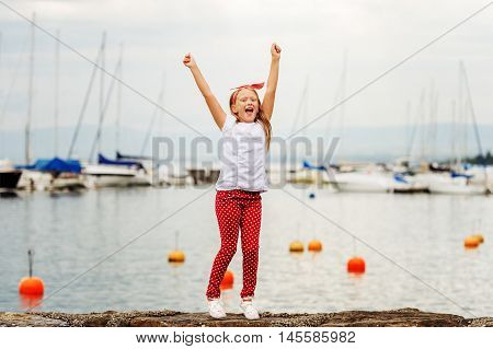 Happy girl  9 year old having fun outdoors, playing by lake on a nice warm sunny evening, wearing white t-shirt and shoes, red polka dot trousers and headband. Image taken at Lake Geneva, Switzerland