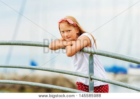 Outdoor portrait of a cute 9 year old girl on a bridge at a port, leaning on the railings with boat on background