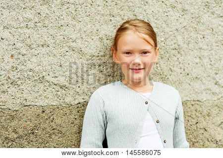 Close up portrait of a cute little girl of 8-9 years old, wearing grey  knitted jacket
