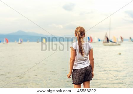 Cute little girl resting by the lake, admiring many sailing boats