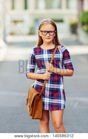 Pretty little 9 year old girl walking back to school, wearing glasses, plaid dress and brown leather bag