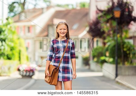 Pretty little 9 year old girl walking back to school, wearing plaid dress and brown leather bag
