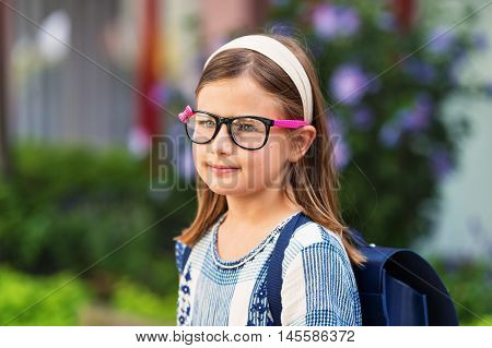 Pretty little 9 year old girl walking back to school, wearing glasses and blue backpack