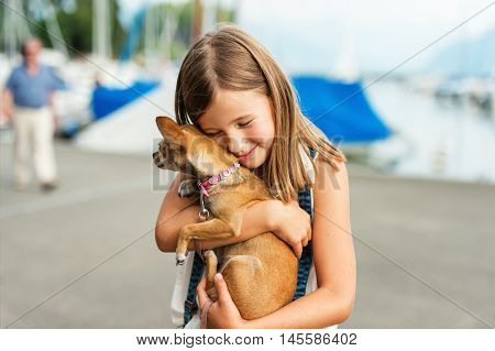 Beautiful little girl hugging little chihuahua dog