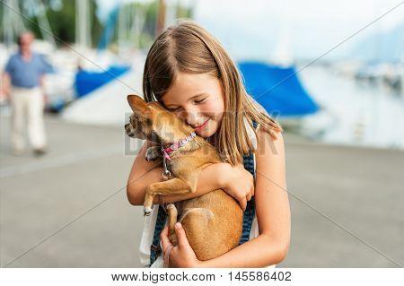 Beautiful little girl hugging little chihuahua dog