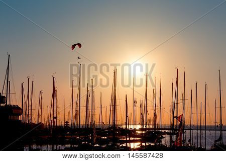 Sunset paragliding over yachts silhouette and sun sea