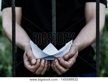 Teenager standing behind iron bars. Two hands holding a boat made out of paper.