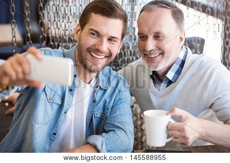 Full of joy. Cheerful content smiling man and his grandfather sitting at the table and expressing positivity while making selfies