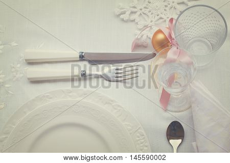 Stainless knife with fork on white tablecloth with christmas decorations, glasses and plates, retro toned